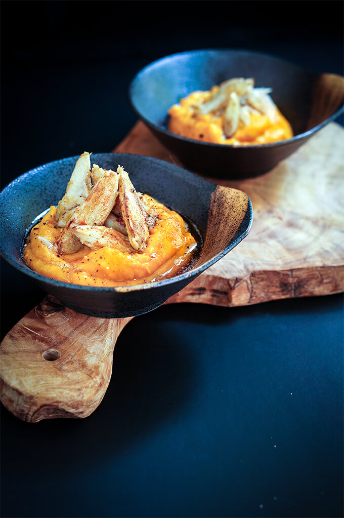 Tender crab meat is sauteed in garlic butter, and served over roasted squash and coconut puree for a luxurious appetizer. | www.viktoriastable.com