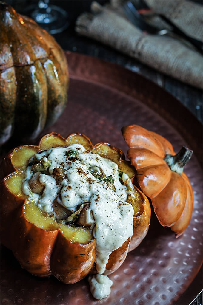 Stuffed pumpkin with bacon, leeks, and scallops, smothered in cheesy bechamel sauce, and a touch of cinnamon! Try this festive Thanksgiving recipe that's not only a feast for your eyes but it's super delicious too! | www.viktoriastable.com