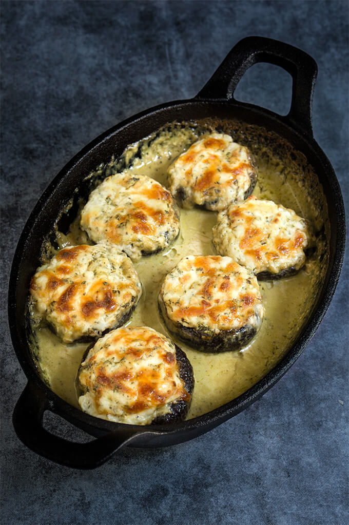 Stuffed mushrooms with prosciutto and ricotta, baked in super delicious, creamy pesto sauce! | www.viktoriastable.com