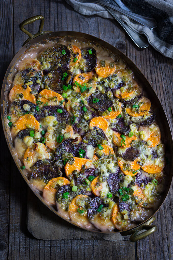 Sweet potato blue cheese gratin - layers of purple and orange sweet potatoes, melting in a pool of spicy cream, and salty blue cheese - this luscious, festive-looking dish will make a bold statement on your Thanksgiving table. | www.viktoriastable.com