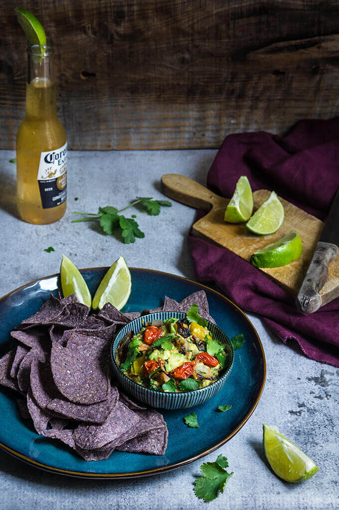 Roasted vegetable guacamole - this slight twist on the beloved avocado dip is bursting with lovely charred flavors of sweet caramelized onions, tomatoes and jalapenios, smoky cumin, and brigth citurs and floral notes from the lime and cilantro. | www.viktoriastable.com