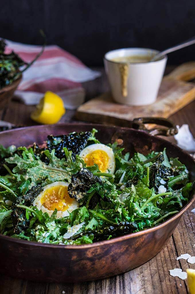 Kale salad with low fat Caesar dressing - baby kale and roasted kale chips, garlicky bread crumbs, and soft boiled eggs, drizzled with a healthy Caesar dressing which is packed with protein, low in fat, yet creamy and robust in flavor. | www.viktoriastable.com
