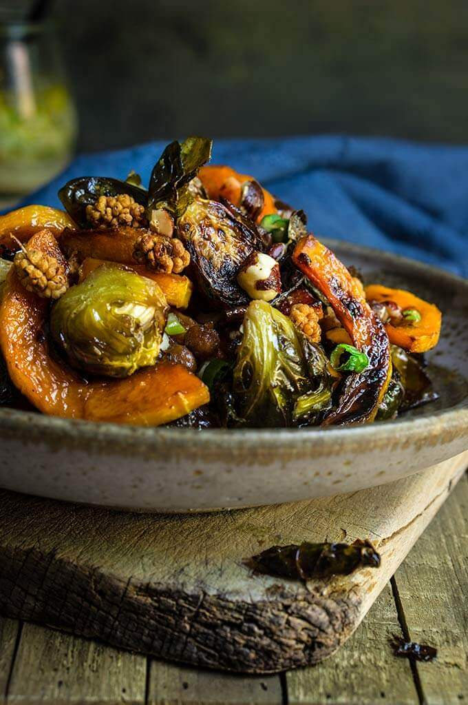 Roasted brussels sprouts and squash salad with horseradish dressing - this warm salad combines all the favorite flavors of fall - the sweetness of roasted veggies and dry fruit, with crunchy nuts, and a pungent horseradish dressing that ties them all in. | www.viktoriastable.com