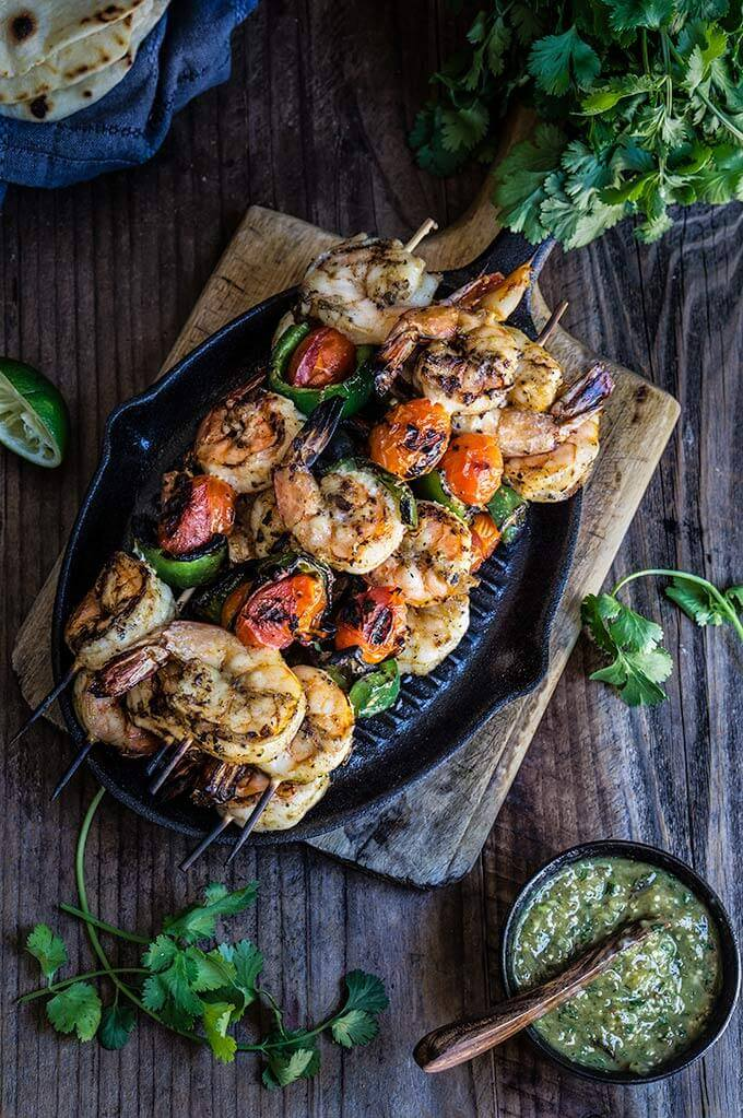 Grilled shrimp tacos with tomatillo salsa and homemade tortillas - bursting with flavor, juicy shrimp, grilled ppoblano peppers and tomatoes, topped with freshly made salsa verde, and served over soft homemade flour tortillas. | www.viktoriastable.com
