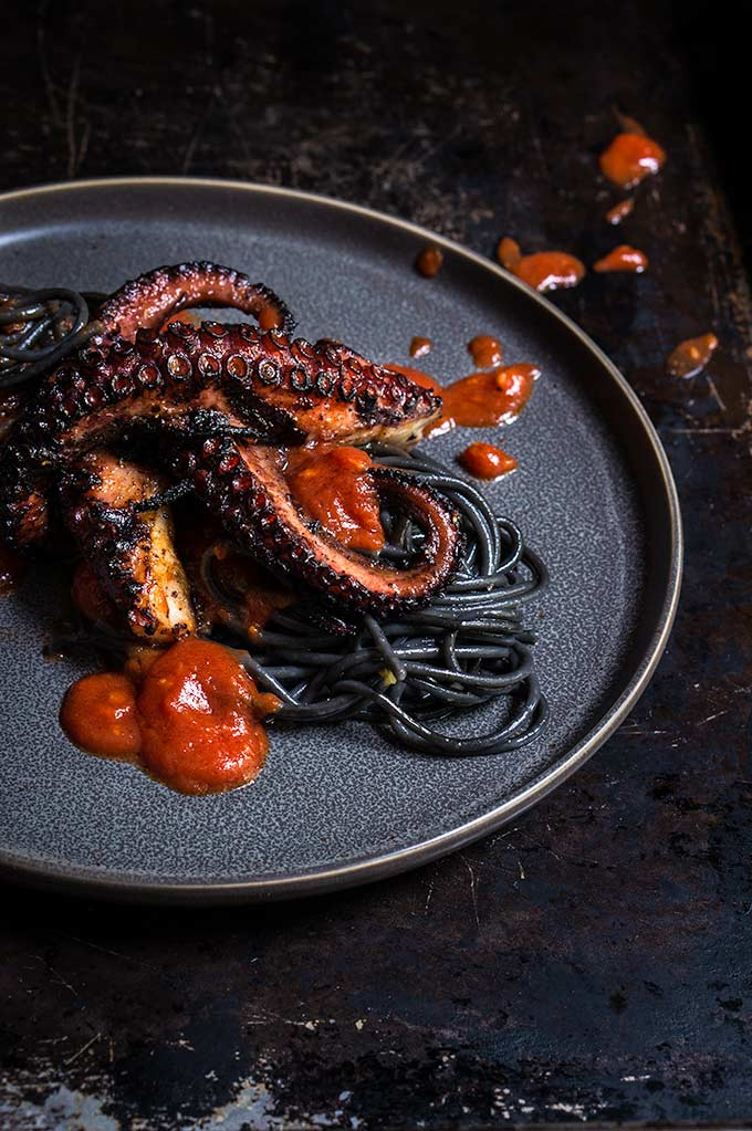 Grilled octopus over squid ink pasta and tomato garlic sauce | www.viktoriastable.com