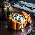 Stuffed pumpkin with bacon, leeks, and scallops, smothered in cheesy bechamel sauce.
